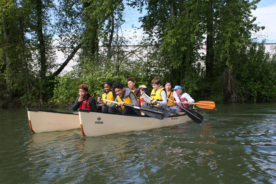 A group of George Middle School students laugh as they paddle on two canoes on the Columbia Slough at Kelly Point Park. The Columbia Slough Watershed Council offers many recreational opportunities like paddle programs and Slough School.