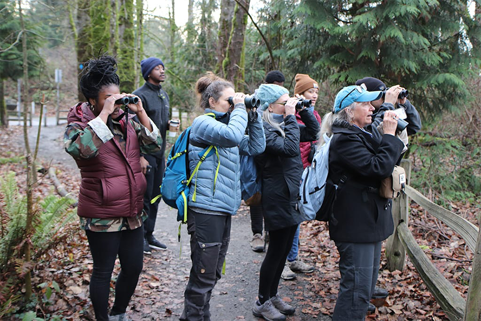 A group of eight adults hold binoculars to their eyes while watching birds in a Portland natural area.