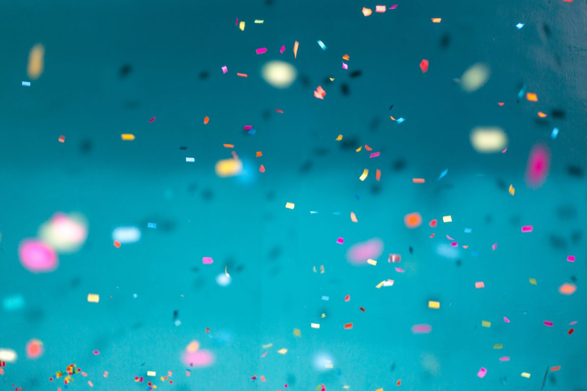 Confetti falls with an aqua background.
