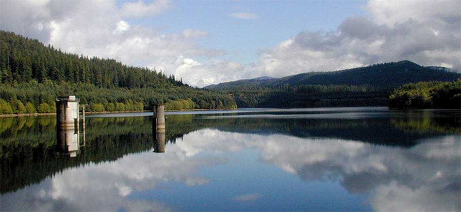 A Bull Run reservoir is surrounded by mountains and conifer trees. The reservoir contains two towers for drinking water extraction