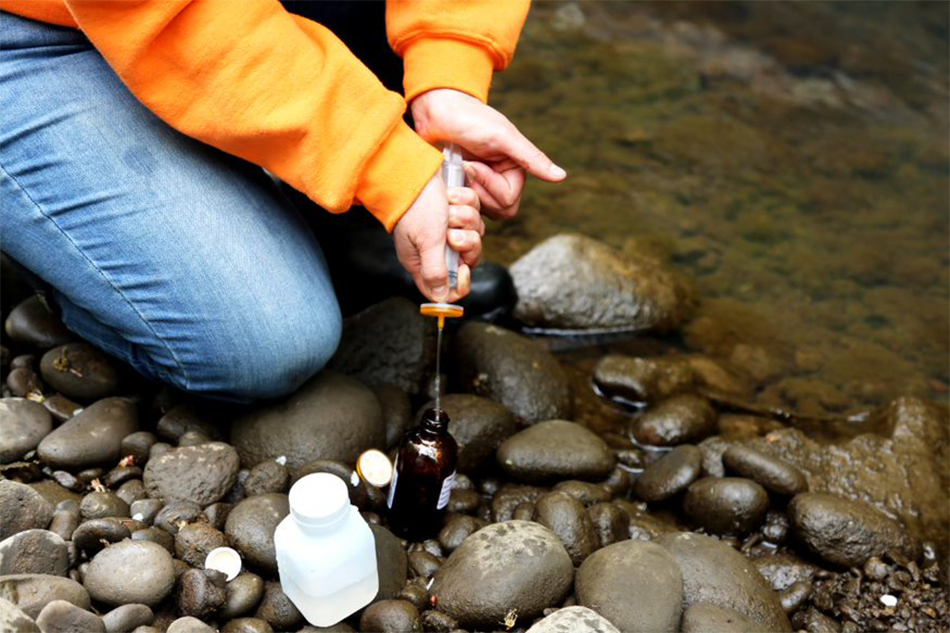 A person kneels on a river rock near a stream, using a syringe to transfer stream water into a testing kit.