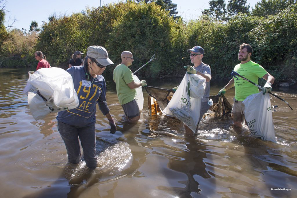 A group of community members carry trash bags filled with waste while standing knee deep in Johnson Creek at the annual Johnson Creek Clean Up.