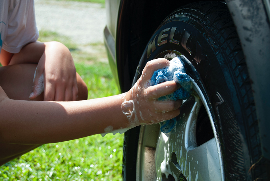 A person washes a car's tire hub with a soapy sponge over a lawn