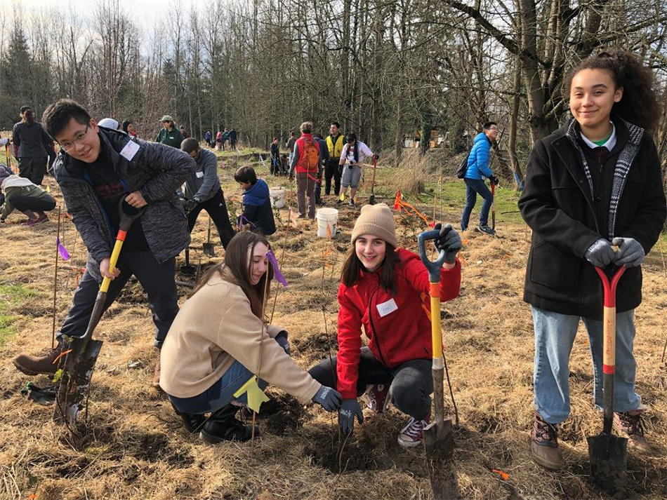 Four teens dig holes for a green space planting with local nonprofit Friends of Trees.