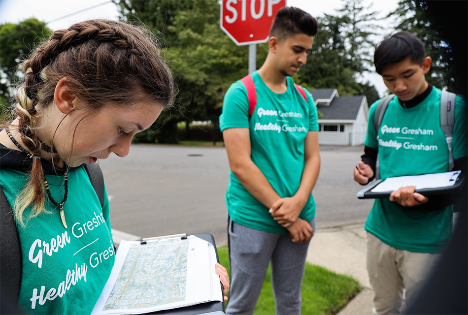 Three teens in 'Green Gresham, Healthy Gresham' shirts look at a map of local residents to visit on a canvassing trip.
