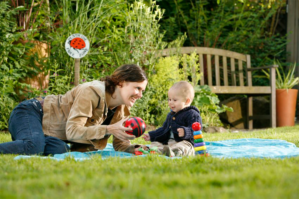 A mother and baby play on a pesticide-free lawn beside their Pesticide Free Zone sign.