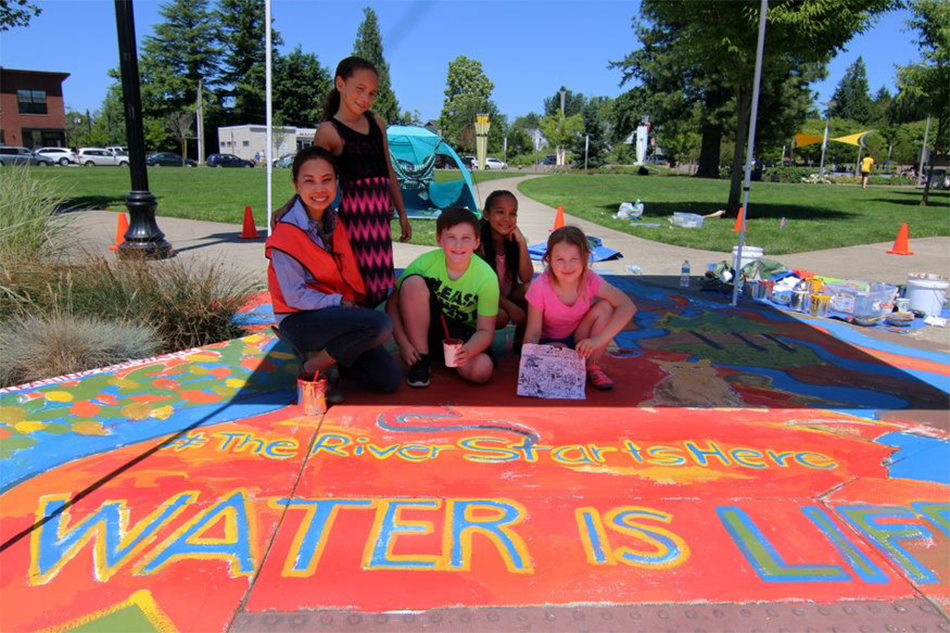 ": Five youth show off a colorful pavement mural that reads ""water is life"""