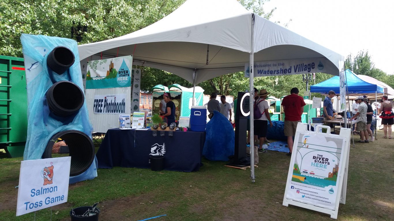 A canopy covers a informational booth for The River Starts Here in an open field. The booth is framed by a colorful sign and Salmon Toss Game, inviting community members to learn more about their watershed.
