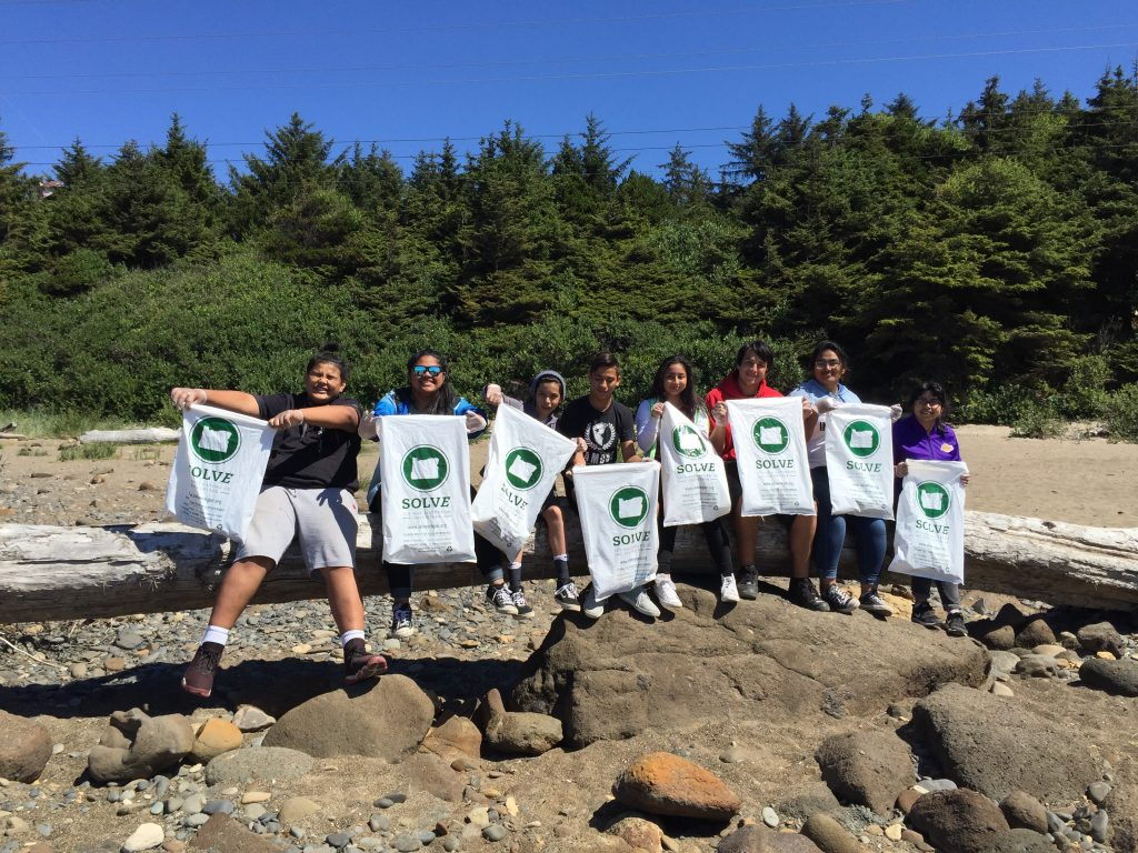 A group of eight people holding up SOLVE trash bags filled with materials found in the wilderness on Sauvie Island.
